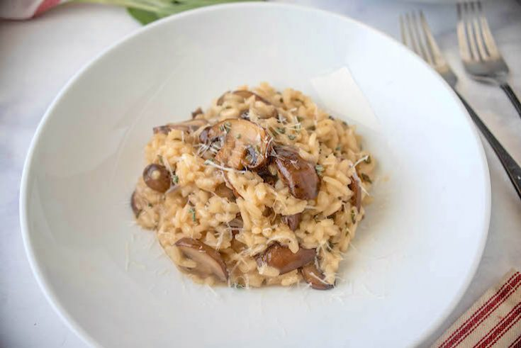 Brown butter mushroom sage risotto is served on a white plate with forks