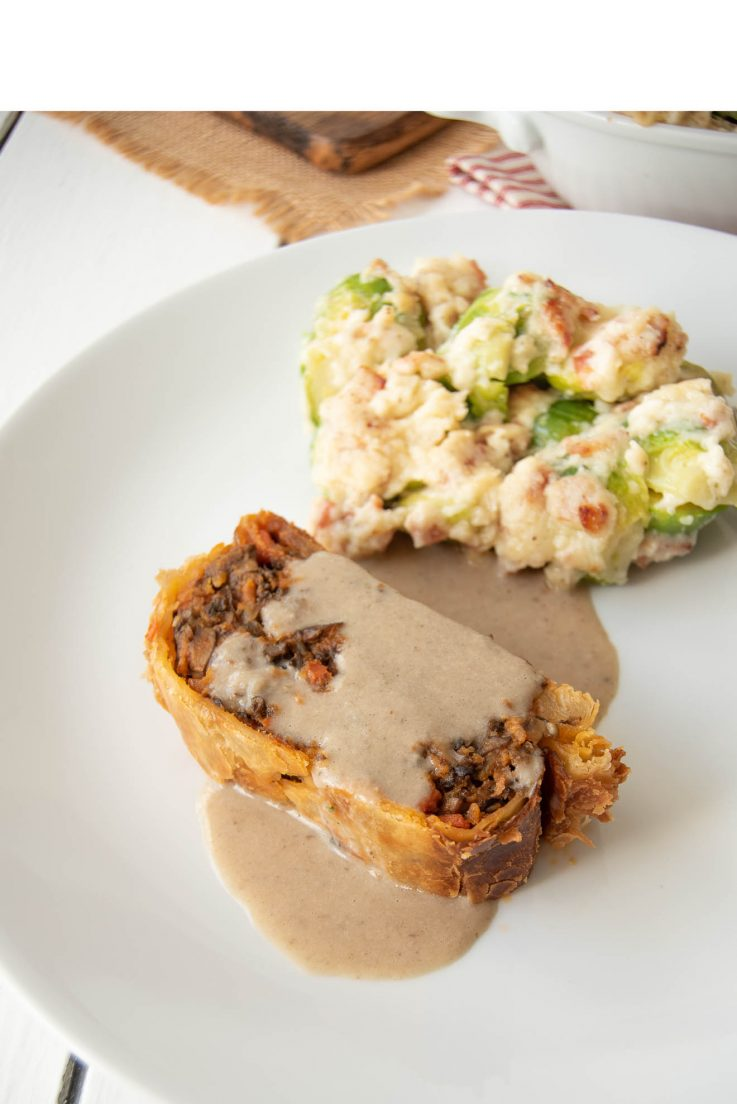 A slice a of mushroom wellington and brussels sprouts and bacon gratin on a white plate