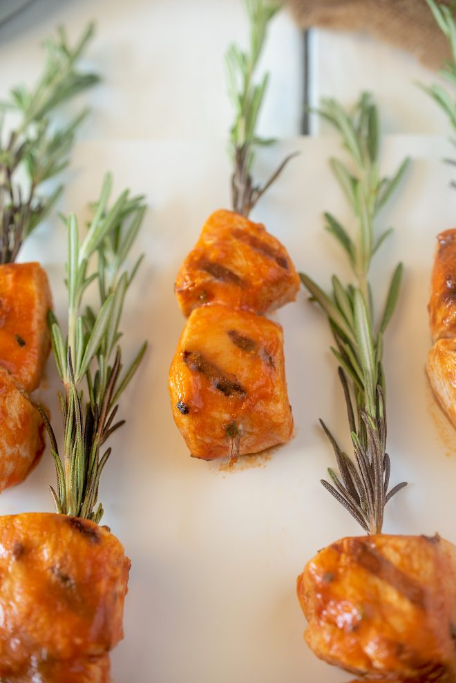 A closeup showing the buffalo chicken grill marks and fresh rosemary sprigs