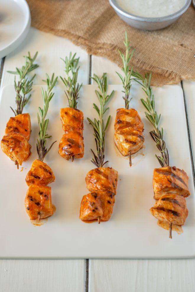 Pieces of chicken coated in buffalo sauce skewered onto fresh rosemary sprigs lying on a square white plate