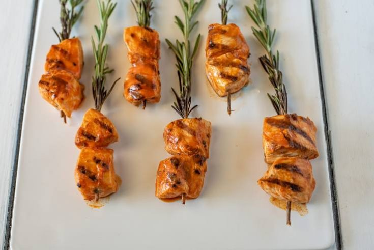 Grilled chicken with buffalo sauce skewered on rosemary sprigs