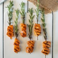 Rosemary skewered chicken served on a white platter with dipping sauce viewed from overhead