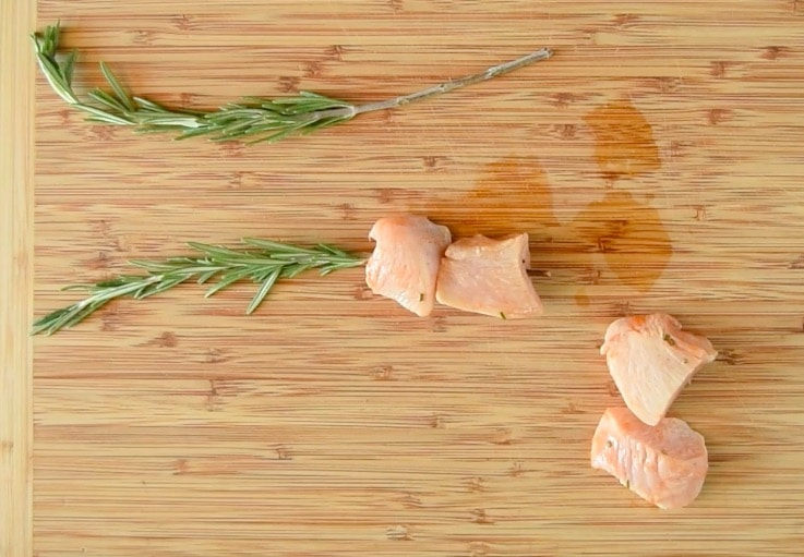 Chicken pieces are skewered onto rosemary sprigs on a cutting board
