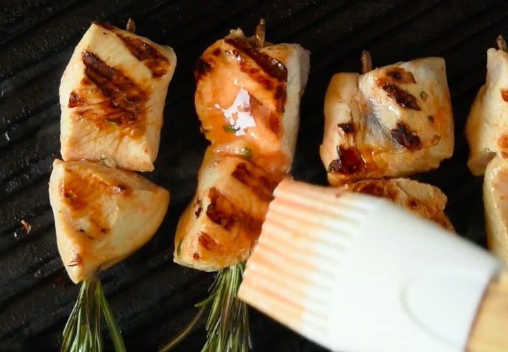 Buffalo rosemary chicken skewers on the grill being brushed with buffalo sauce