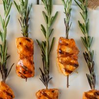 Rows of grilled buffalo chicken threaded onto fresh rosemary sprigs
