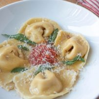 Fresh pasta folded into cappellacci shape to look like nuns hats with brown butter, crispy sage, red pasta sauce and grated Parmesan cheese