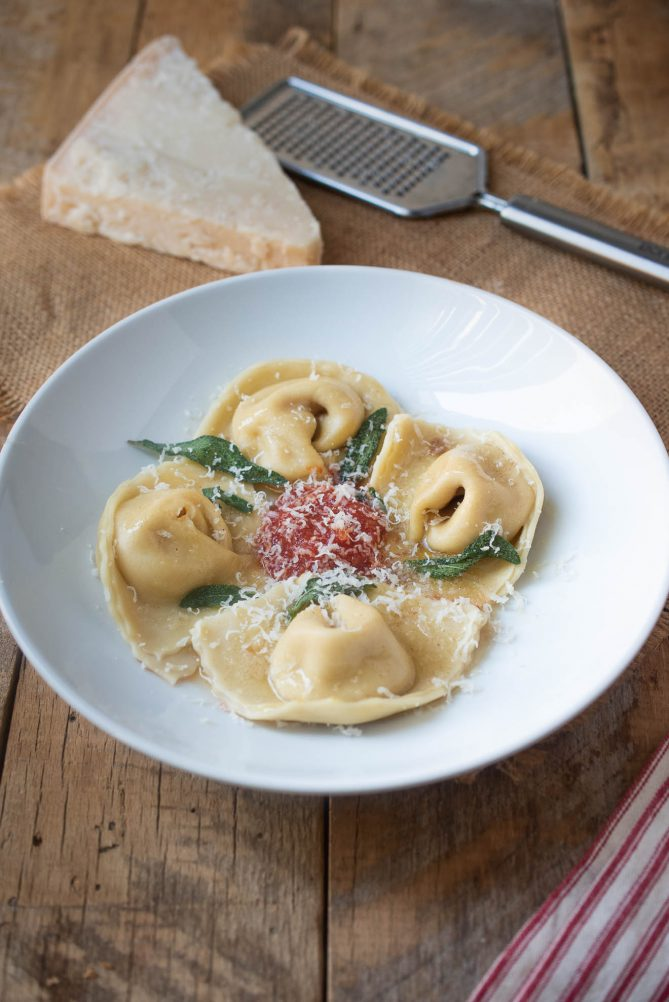Grated parmesan cheese lightly covering butternut squash filled pasta with fresh sage leaves