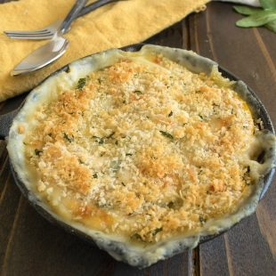 A cast iron skillet of butternut squash and sage gratin with serving spoons