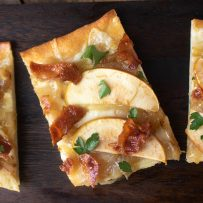 A rectangle shaped piece of flatbread with 2 apple slices, crispy bacon bits and chopped parsley