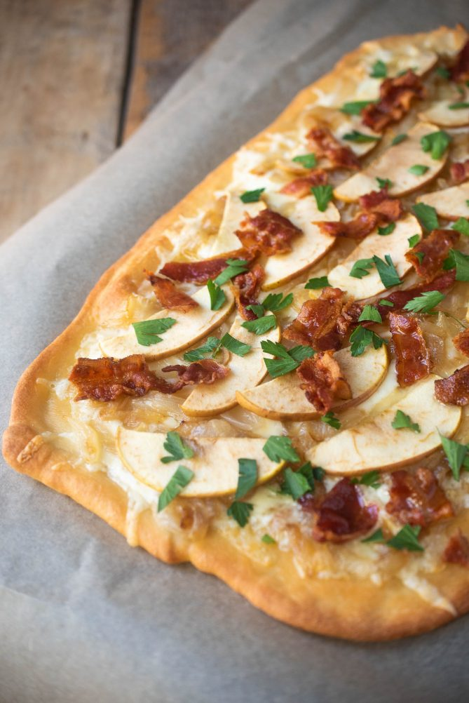 A closeup of the crispy brown edges of flatbread topped with melted fontina, caramelized onions apple slices and crispy bacon.