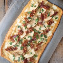 A caramelized onion apple and bacon flatbread pizza from overhead on a baking sheet shaped in a long rectangle
