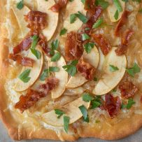 A closeup of the topping on a flatbread pizza of fontina cheese, apple, caramelized onions, bacon pieces and green parsley