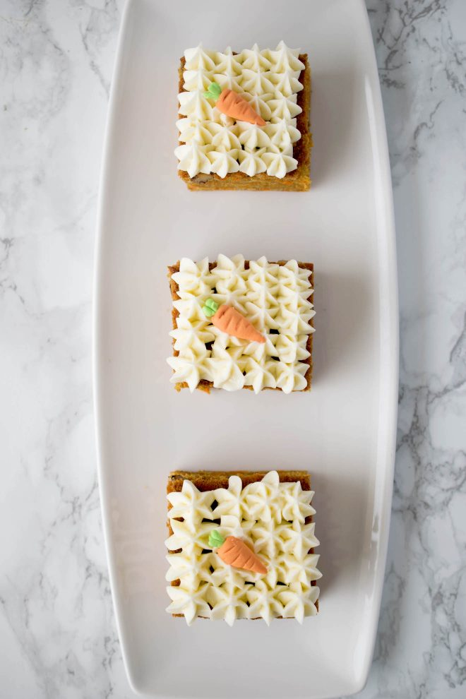 3 carrot cake slices on a white oblong plate