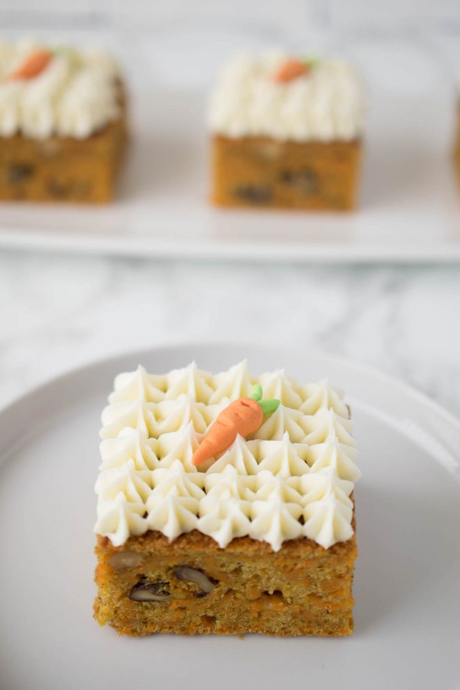 A slice of carrot cake square with decorative frosting on a white plate