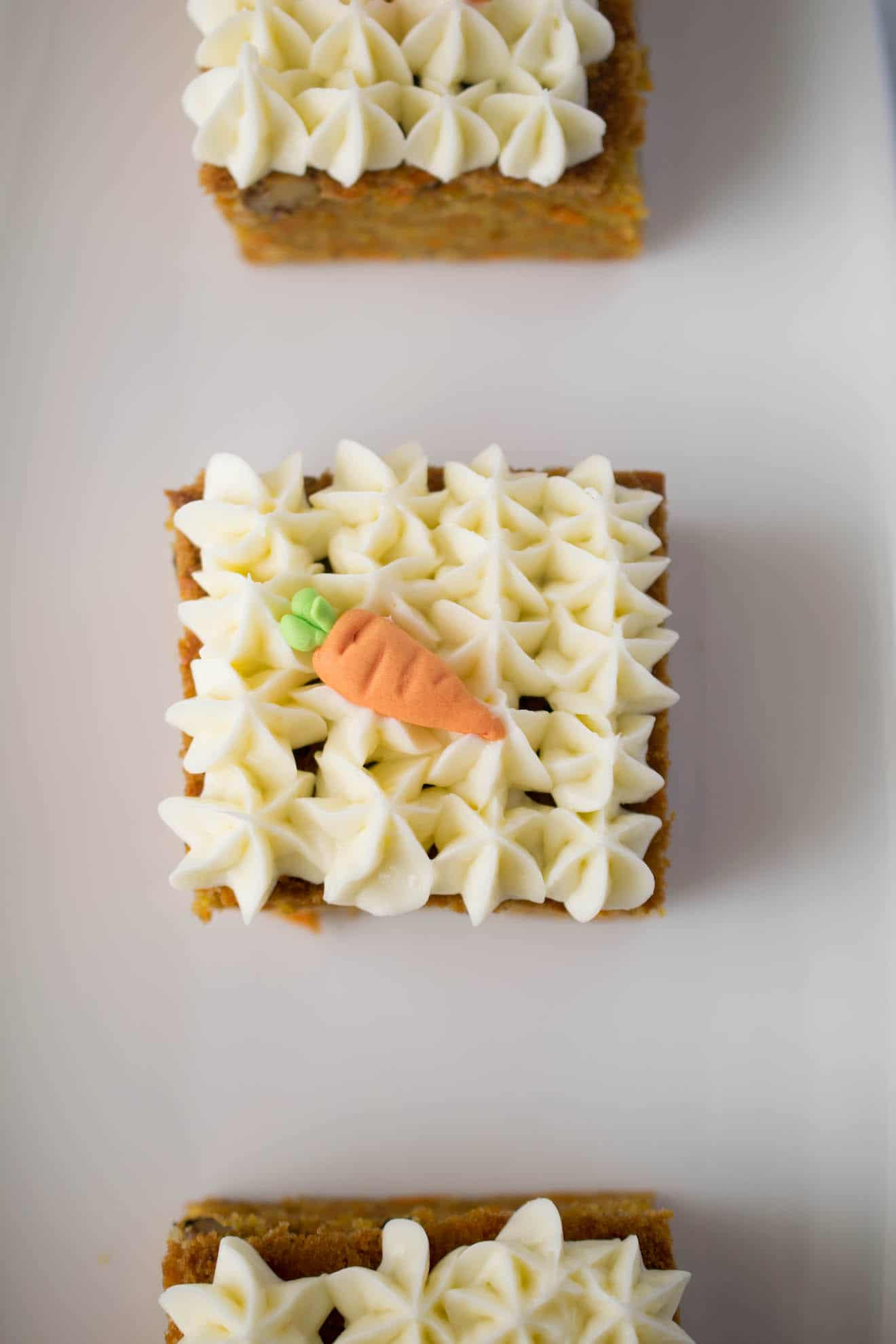 Pretty piped cream cheese frosting on top of carrot cake with a decorative sugar carrot