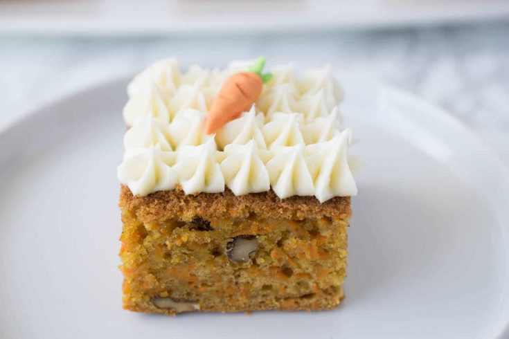 A square of carrot cake topped with cream cheese frosting and a decorative carrot