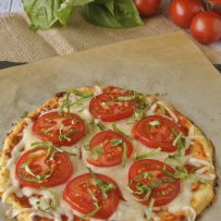 Slices of tomato and shredded basil on a cauliflower crust pizza