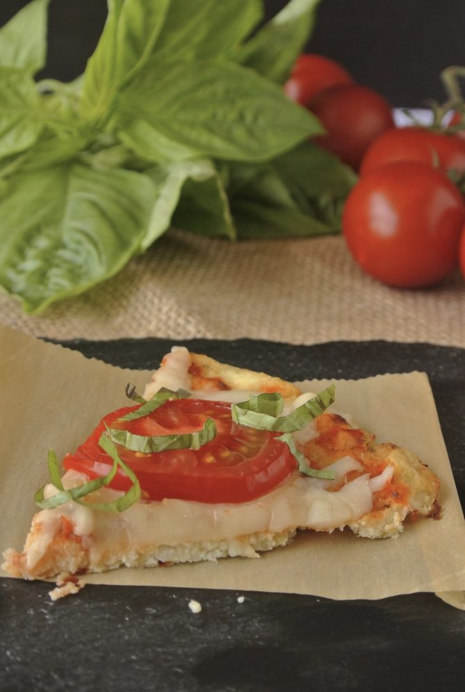 A slice of cauliflower crust pizza topped with cheese, tomato and basil