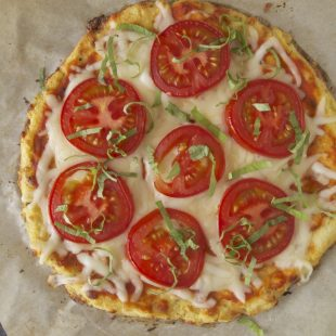 Cauliflower crust tomato basil pizza viewed from overhead