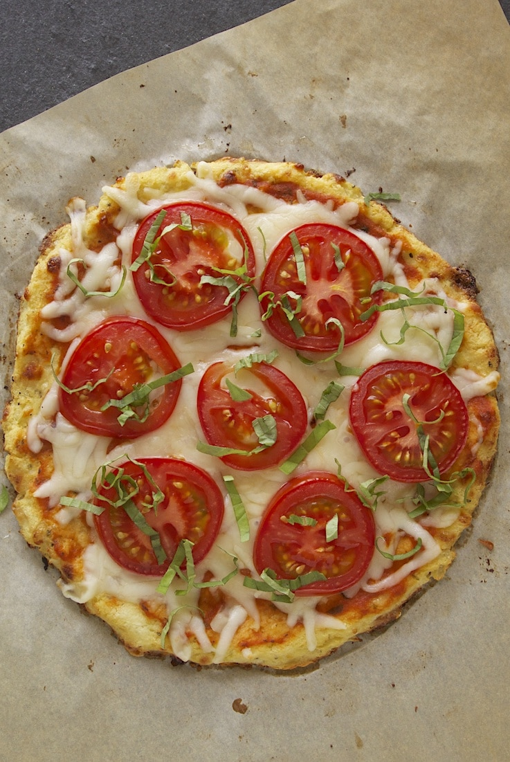 An overhead image of the pizza showing the beautiful red tomatoes and green basil