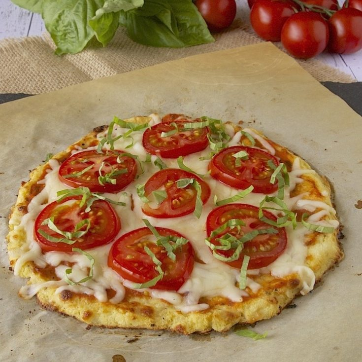 Cauliflower Crust pizza topped with tomato slices and chopped basil
