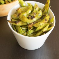 An angled white bowl filled with charred edamame