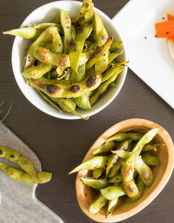 A white bowl and a wooden bowl filled with charred edamame with some spilling out