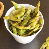 Cooked edamame in a bowl topped with togarashi spice and black sesame seeds