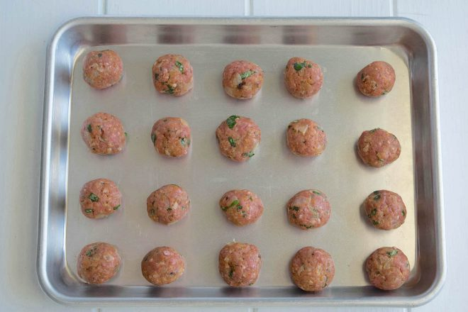 Uncooked meatballs on a baking sheet ready for the oven