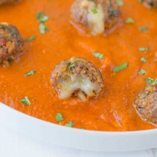 A closeup of a mini meatballs showing the melted cheese inside
