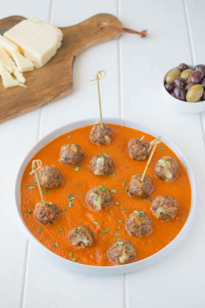 A round platter of mini meatballs in tomato sauce