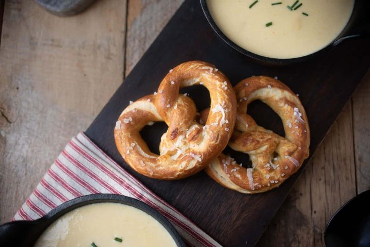 2 cheese stuffed pretzels on a board served with soup