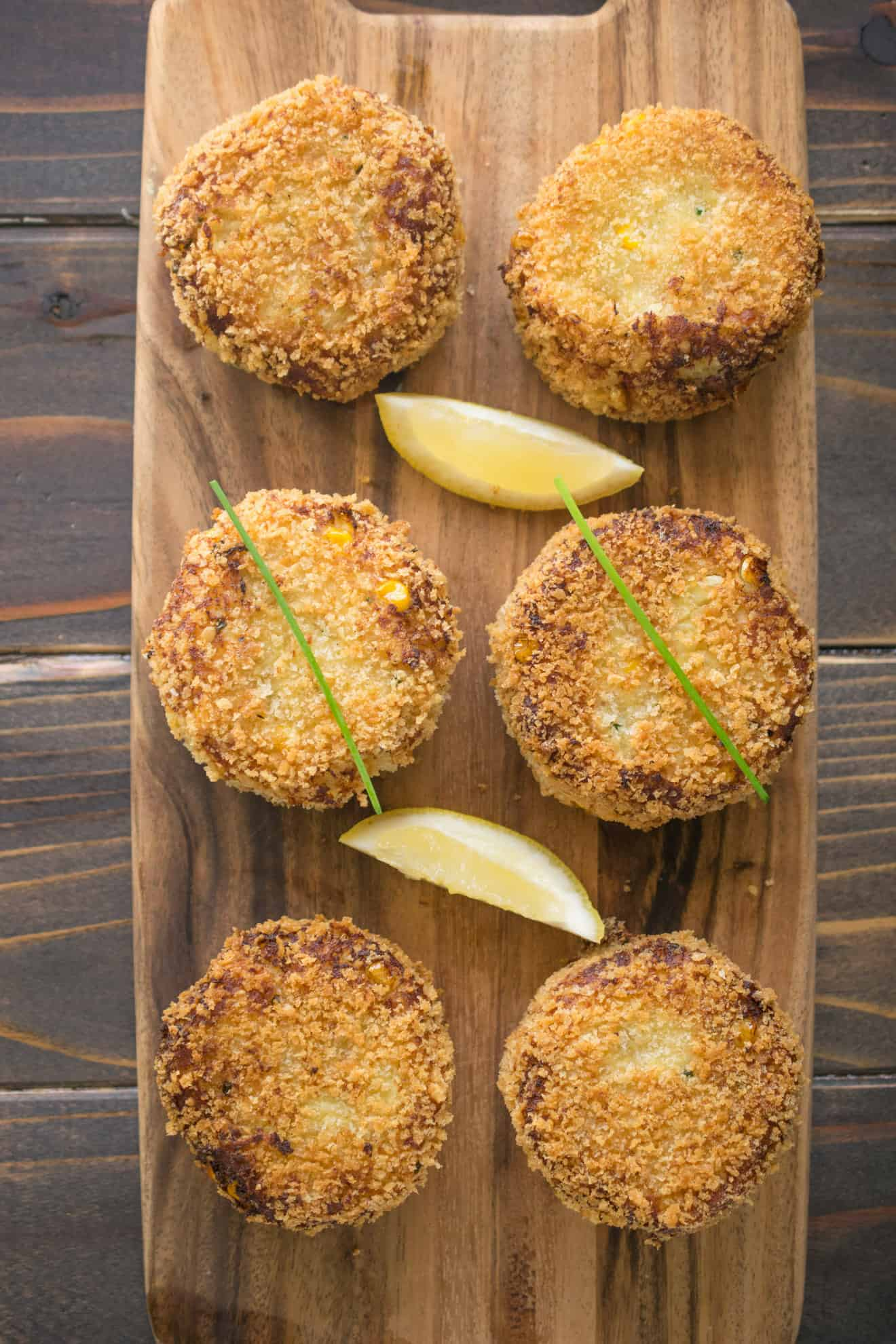5 cheesy tuna melt cakes on a serving board with lemon wedges and chives