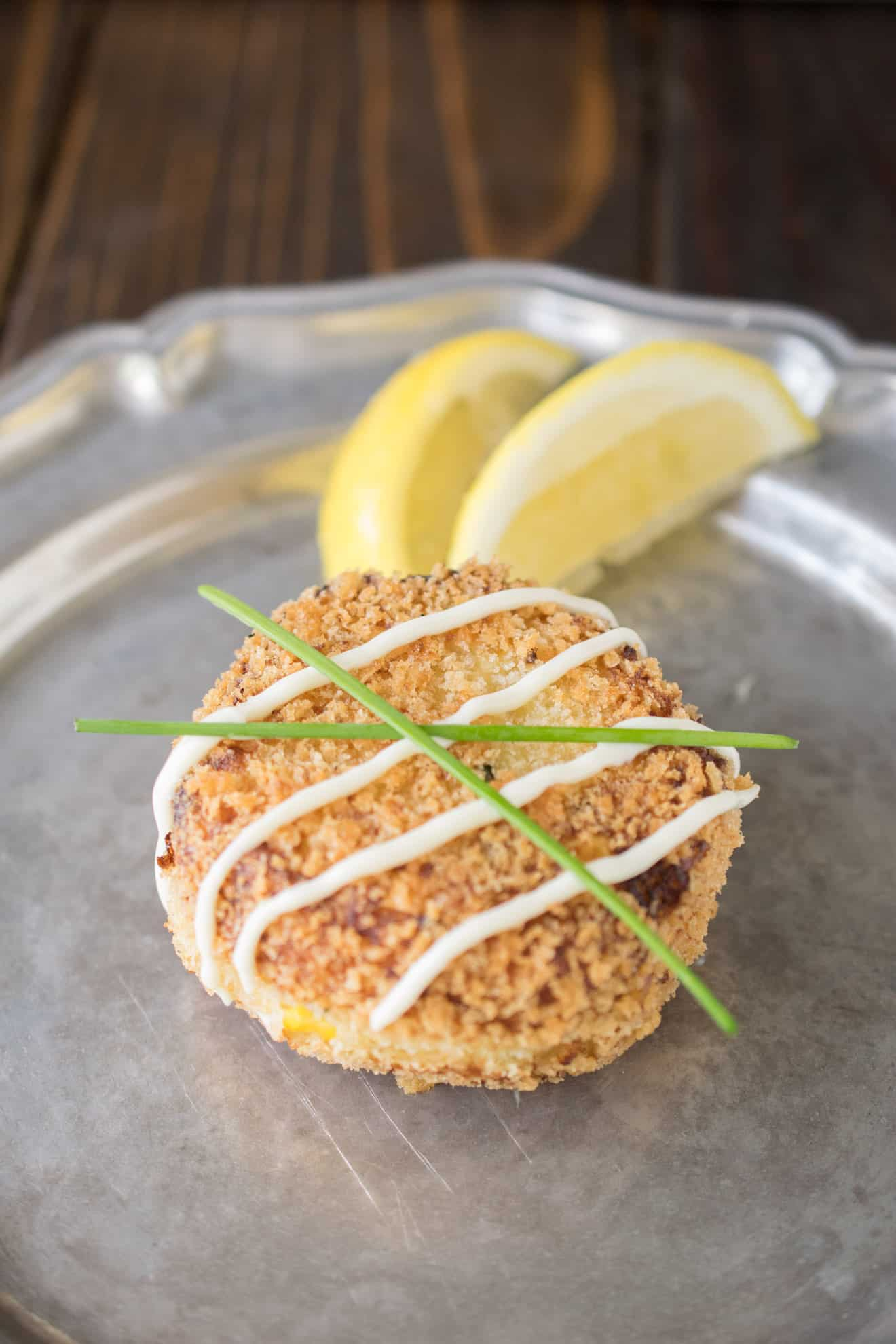 A cheesy tuna melt cake on a plate with a drizzle, chives and lemon