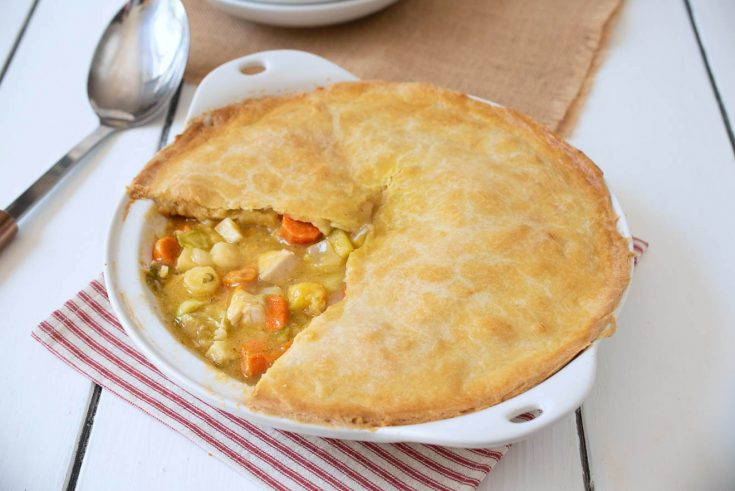 Chicken pot pie showing the filling with chicken and vegetables in a white dish