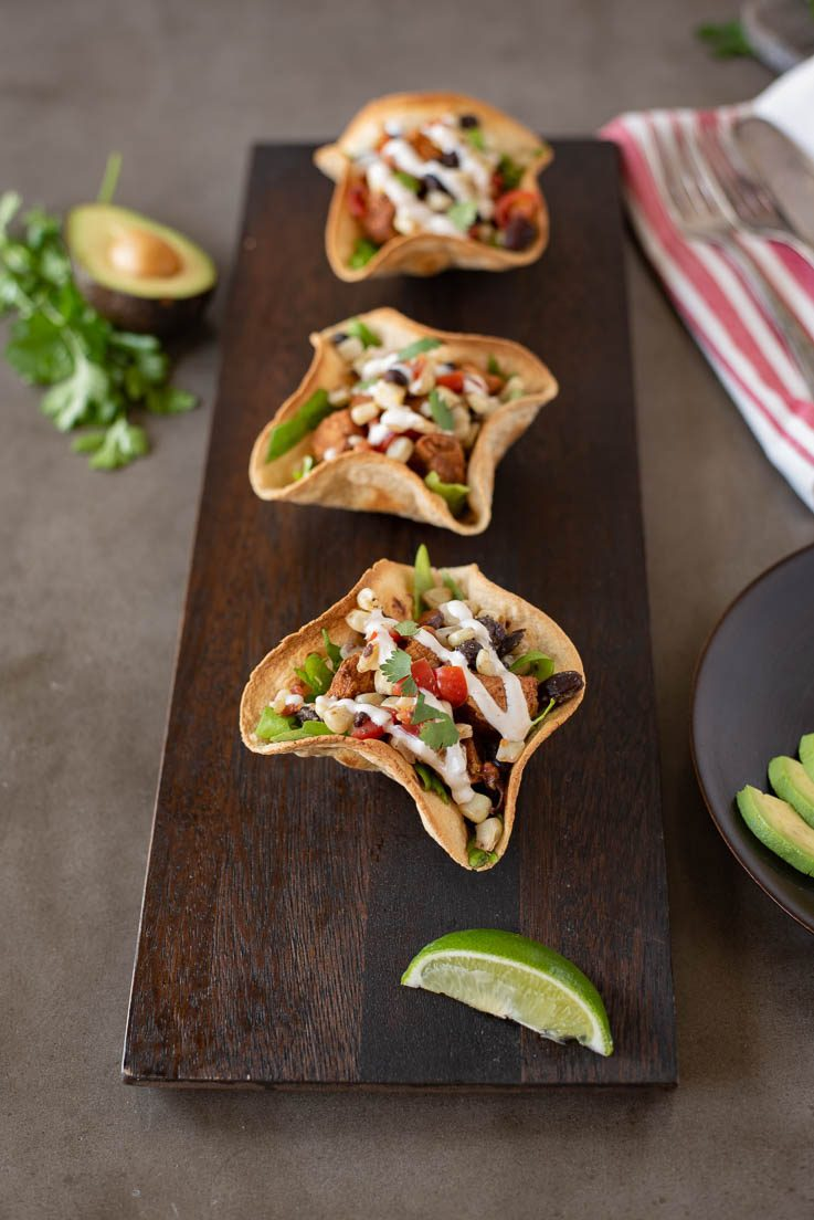 3 chicken tostada salad bowls lined up on a wood board with lime wedge and avocado