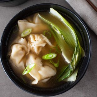 Green bok choy, sliced spring onions and chicken wontons on broth