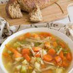 A large white bowl of The Best Chicken Soup with a loaf of crusty bread