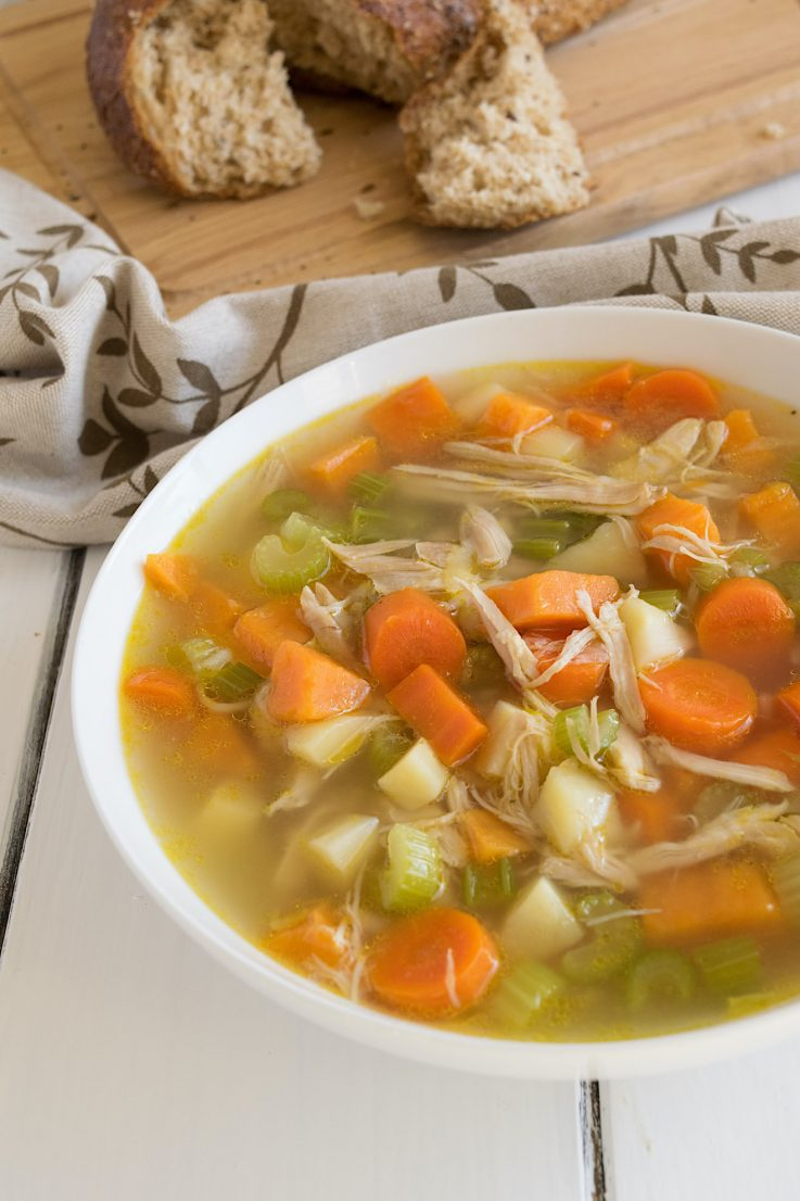 A hearty bowl of chicken soup with carrots, celery and potatoes