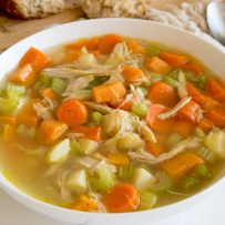 The best chicken soup served in a white bowl with a napkin, spoon and bread