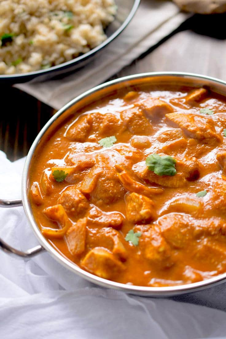 A warm bowl of chicken tikka masala garnished with cilantro