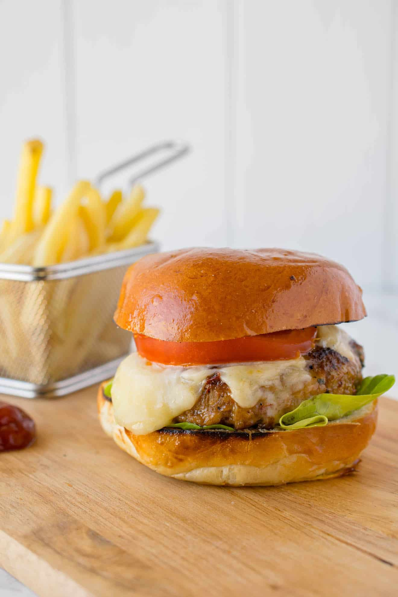 A thick chipotle chicken burger topped with melted cheese, tomato and lettuce