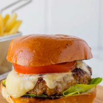 A juicy burger on a bun with melted cheese, lettuce and tomato