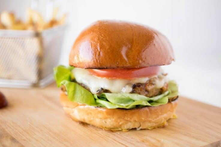 Chipotle chicken burger on a brioche bun with lettuce and tomato