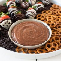 The dip in a white bowl with pretzels for dipping and chocolate covered strawberries