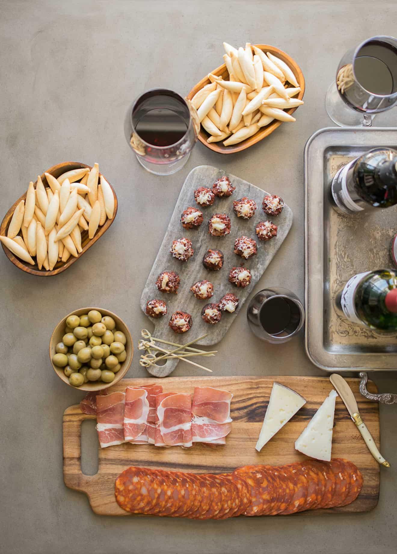 An array of tapas, chorizo stuffed mushrooms, meats, cheeses, crackers and wine