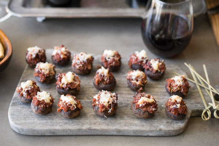 A platter of chorizo stuffed mushrooms with a glass of red wine