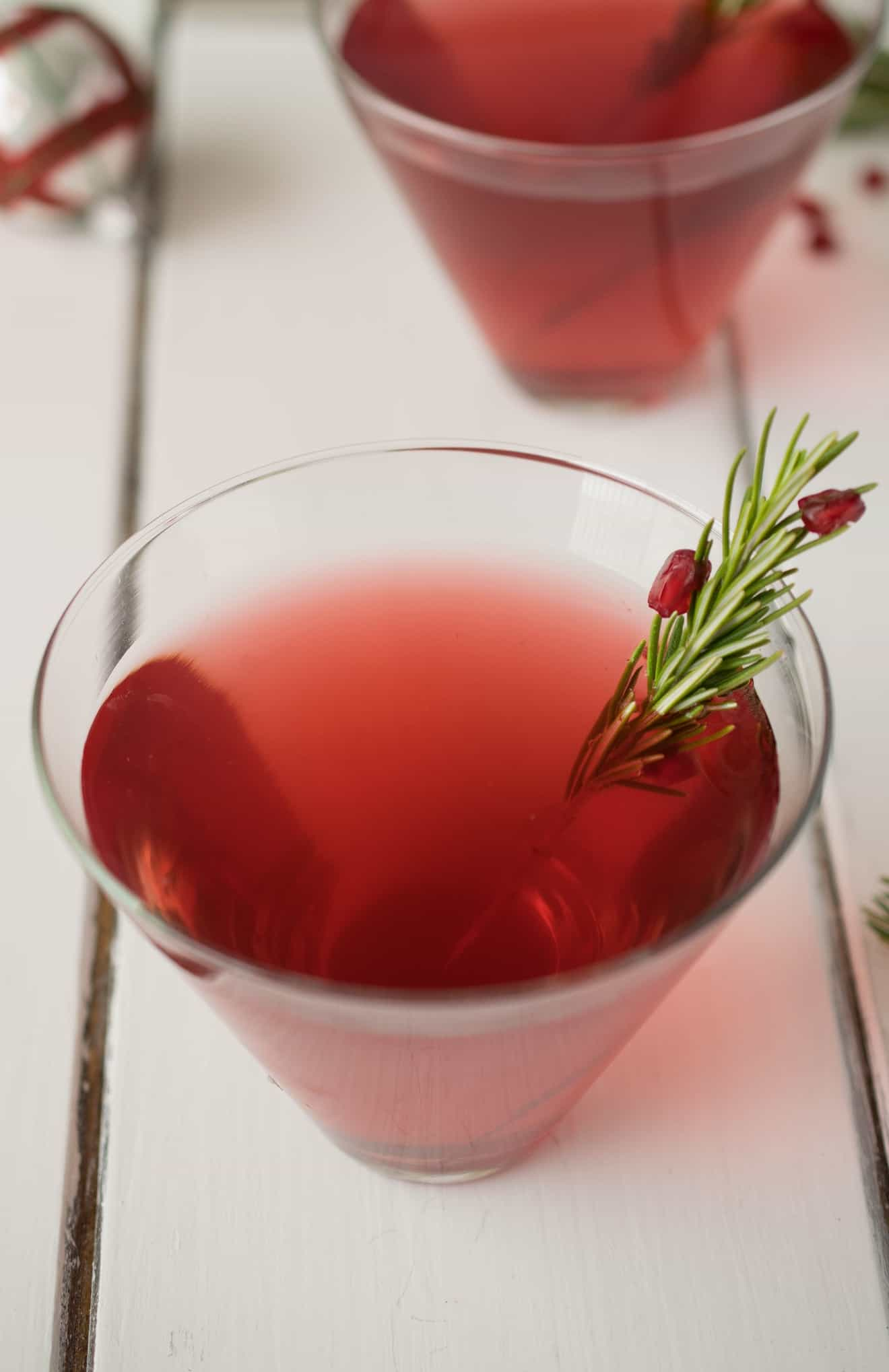 A ruby red drink garnished with fresh rosemary and pomegranate seeds