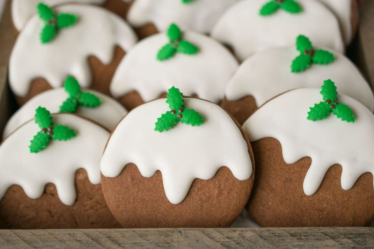 A closeup of the cookies showing the pretty fondant green holly and white frosting