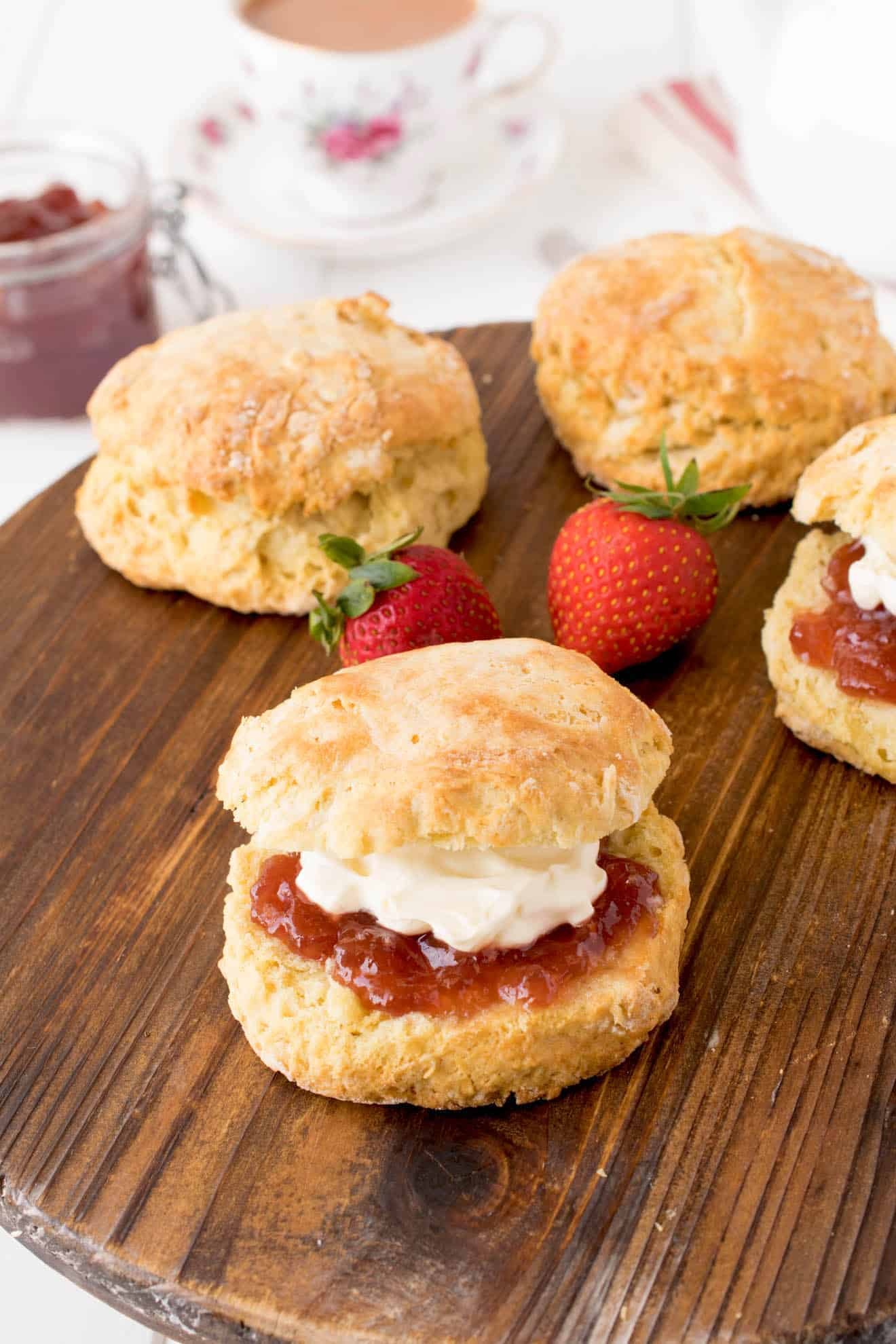 4 English Scones on a board with one sandwiched with jam and clotted cream